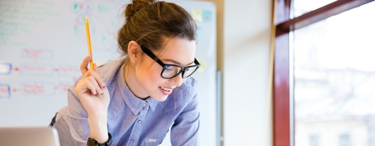 Happy young woman in glasses standing near the window in office and working with blueprint-831521-edited.jpeg
